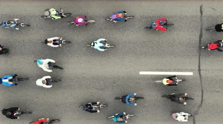 Cyclists ride along the road during the bike ride, aerial view vertically down.
