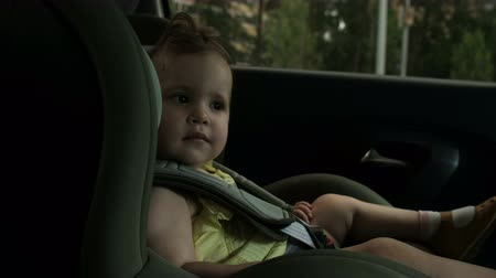 little toddler smiles to camera sitting on child car seat