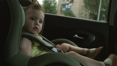 cute little girl drives with family in car child safety seat Stock Footage