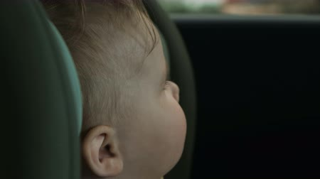 toddler sits in child car safety seat and looks out window
