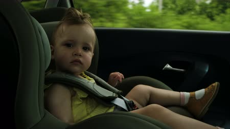 parentes : toddler girl yawns in dark green child car safety seat