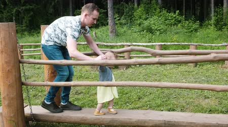 handsome man helps toddler daughter walk along park log
