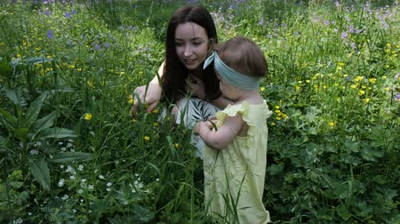 long haired brunette squats near small girl smells flowers