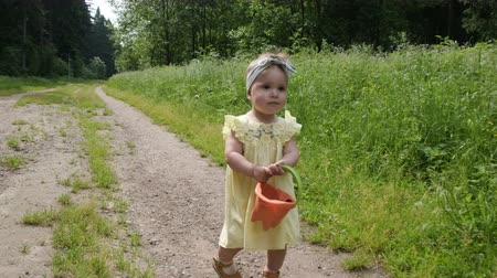 toddler girl in yellow summer dress walks with small bucket