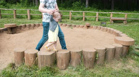 man in t-shirt and jeans helps toddler lady walk on stumps
