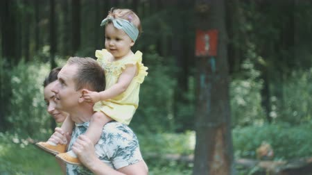 handsome man holds daughter on shoulders wandering in forest