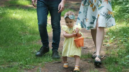 toddler girl in dress holds bucket walking by mother father Stock Footage