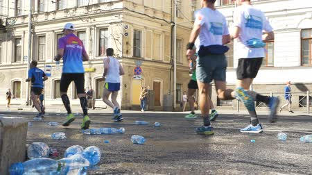 People run a marathon and throw plastic water bottles on the asphalt in slow motion
