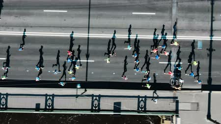 Aerial view of the city marathon, a crowd of people running through the distance, running shadows Stock Footage