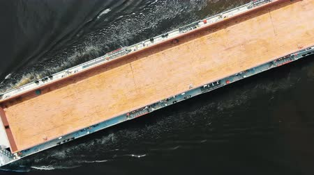 long brown unloaded freight vessel sails on deep water