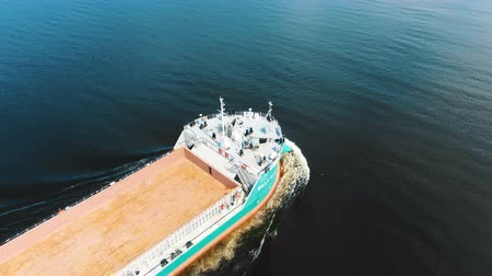 brown unloaded freight vessel sails on deep blue sea water Stock Footage