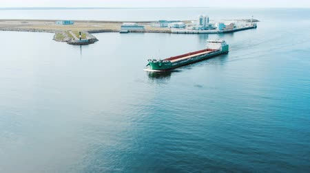 large vessel sails against modern port on island aerial view Stock Footage