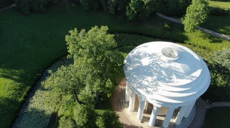 cercar : pictorial gazebo with white columns surrounded by blue river