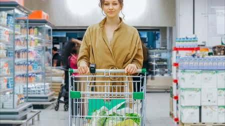 comprador : young woman with shopping cart stands in supermarket