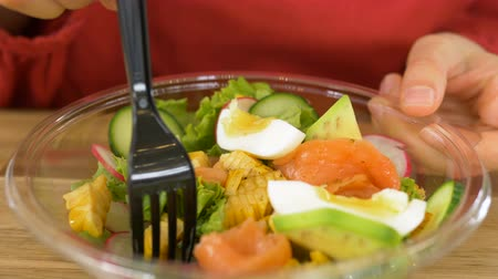 dietético : fastfood cafe customer pierces salad with vegetables, fish and egg with a fork