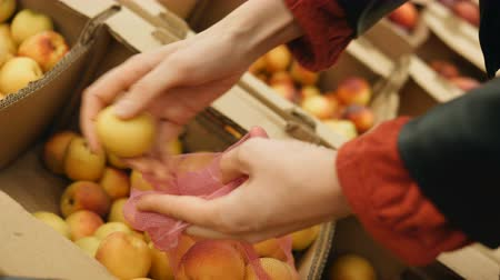 consumo : girl puts apricots in a eco bag in a supermarket Vídeos