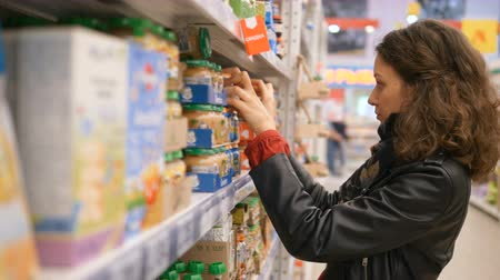 compares : young woman reads concentrated composition on cans of baby food in a supermarket