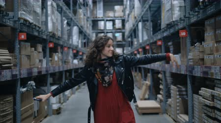 crazy girl : pretty girl dancing a wave with a phone in a large industrial stock room