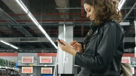 flash sale : young woman types on new smartphone in modern tech shop