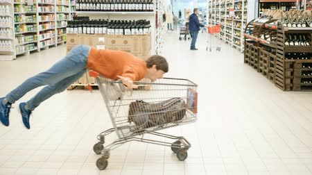 tágas : funny guy drives on shopping cart past product stacks