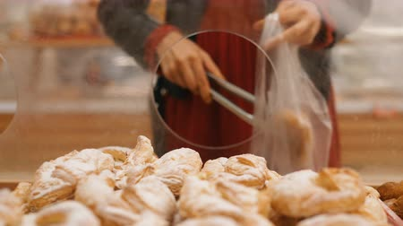 tang : beautiful girl hand takes pastry and puts into plastic bag Stockvideo