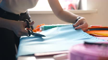 портной : seamstress cuts blue fabric piece with scissors on desk Стоковые видеозаписи