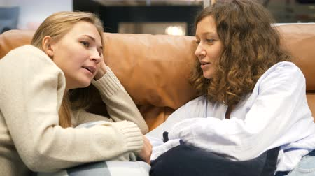 discutir : girls sit on sofa and discuss women topics enjoying rest