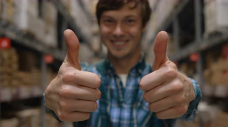 supermarket shelf : guy shows thumbs-up gesture with two hands in storehouse