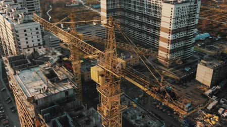 unfinished : cranes work on construction site of new complex building