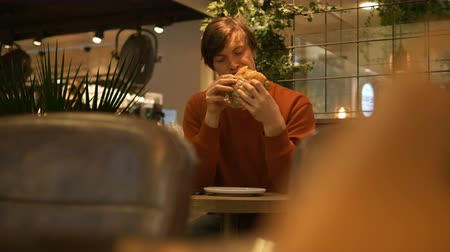 szpinak : handsome man sits at table in cafe and eats fast food