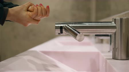 sanitize : woman with long navy coat sleeves washes hands slow motion