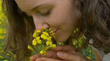 hardal : nice woman with brown curly hair sniffs beautiful canola Stok Video