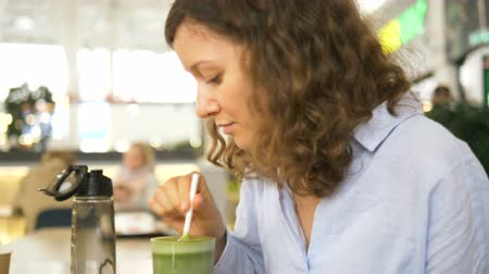 food court : A woman drinks a smoothie from a glass with a straw in a cafe Stock Footage