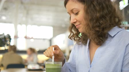 food court : Beautiful kinky girl drinking green smoothie on food court