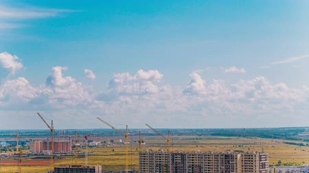 összetett : cranes operate near constructions against yellow fields