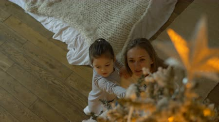 admirar : mom hugs kid admiring Christmas tree with top on foreground