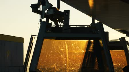 приехать : Skiers come out of the cabins of the ski lift close-up against a Sunny sunset