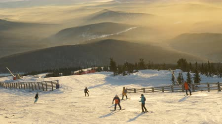 bűbájos : A group of skiers and snowboarders descend the ski slope against the backdrop of a stunning sunset and mountain hills Stock mozgókép