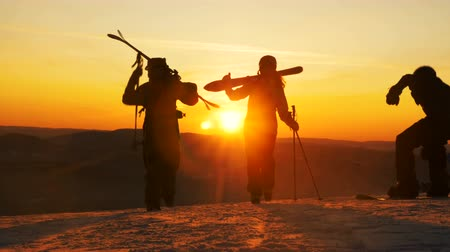 montanhoso : people with ski equipment walk along snowy hilltop at sunset