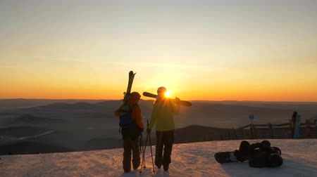 tourist silhouette : skiers walk along snowy hilltop against hills at sunset