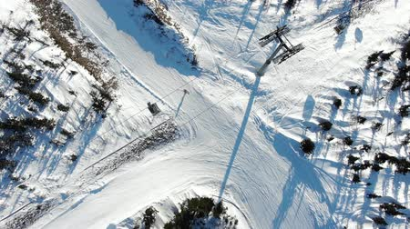 chairlift : modern ski lift moves over skiers on track among trees upper Stock Footage