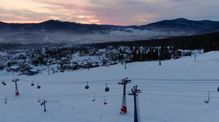 chairlift : ski lift cabins move over tracks at dusk under evening sky
