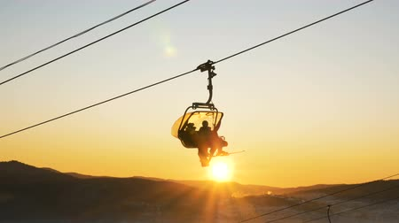 montanhoso : skier silhouettes move on chairlift against setting sun disk