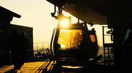 chair lift : active tourist silhouettes get out ski lift cabin at sunset Stock Footage