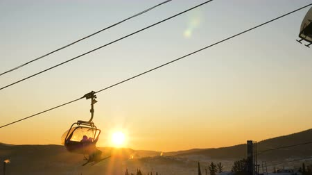 tourist silhouette : skier silhouettes in chairlift move at back bright sunrise