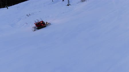 snowcat : modern red snowcat drives up white track under ski lift