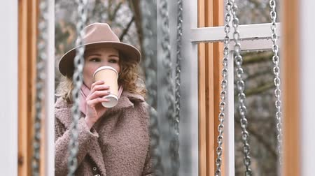 başörtüsü : Young loneley woman in a brown coat, hat and rose scarf drings coffee
