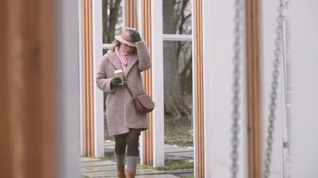 buty : Young loneley woman in a brown coat, hat and rose scarf walking by swings with a cup of coffee Wideo