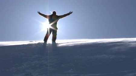 cold : Young Man in a Worship Pose on Top of a Mountain Winter Nature Background HD Stock Footage