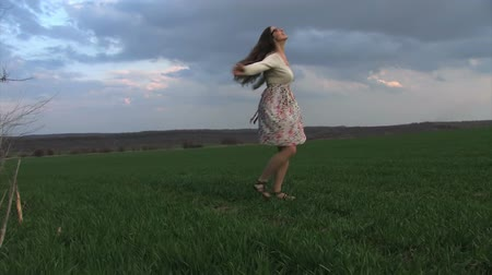 boso : Woman spinning on a spring grass field Wideo